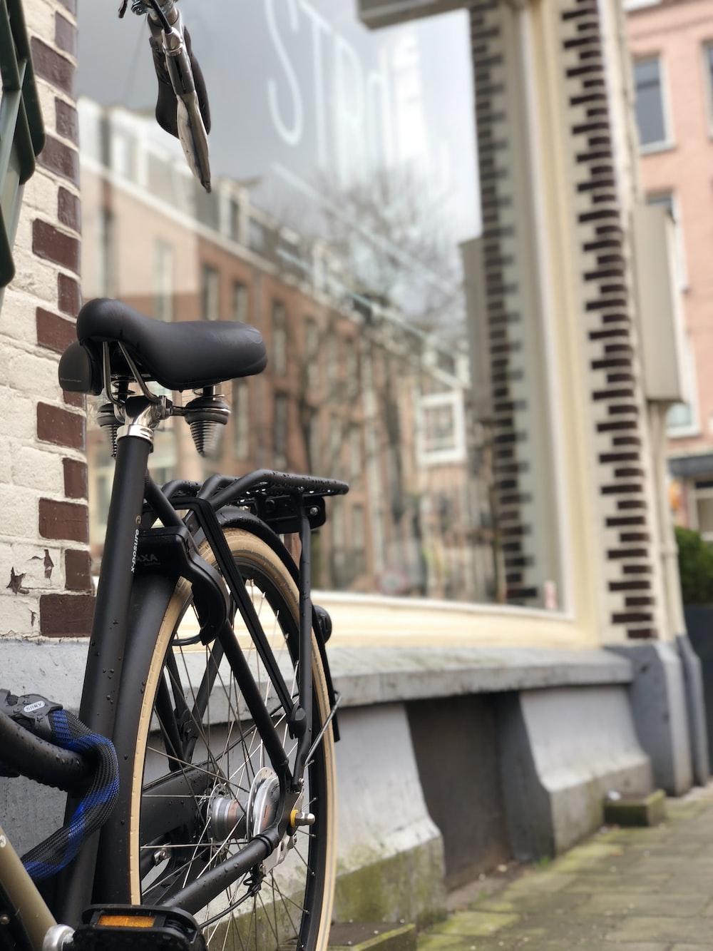 black commuter bike parked beside glass store window