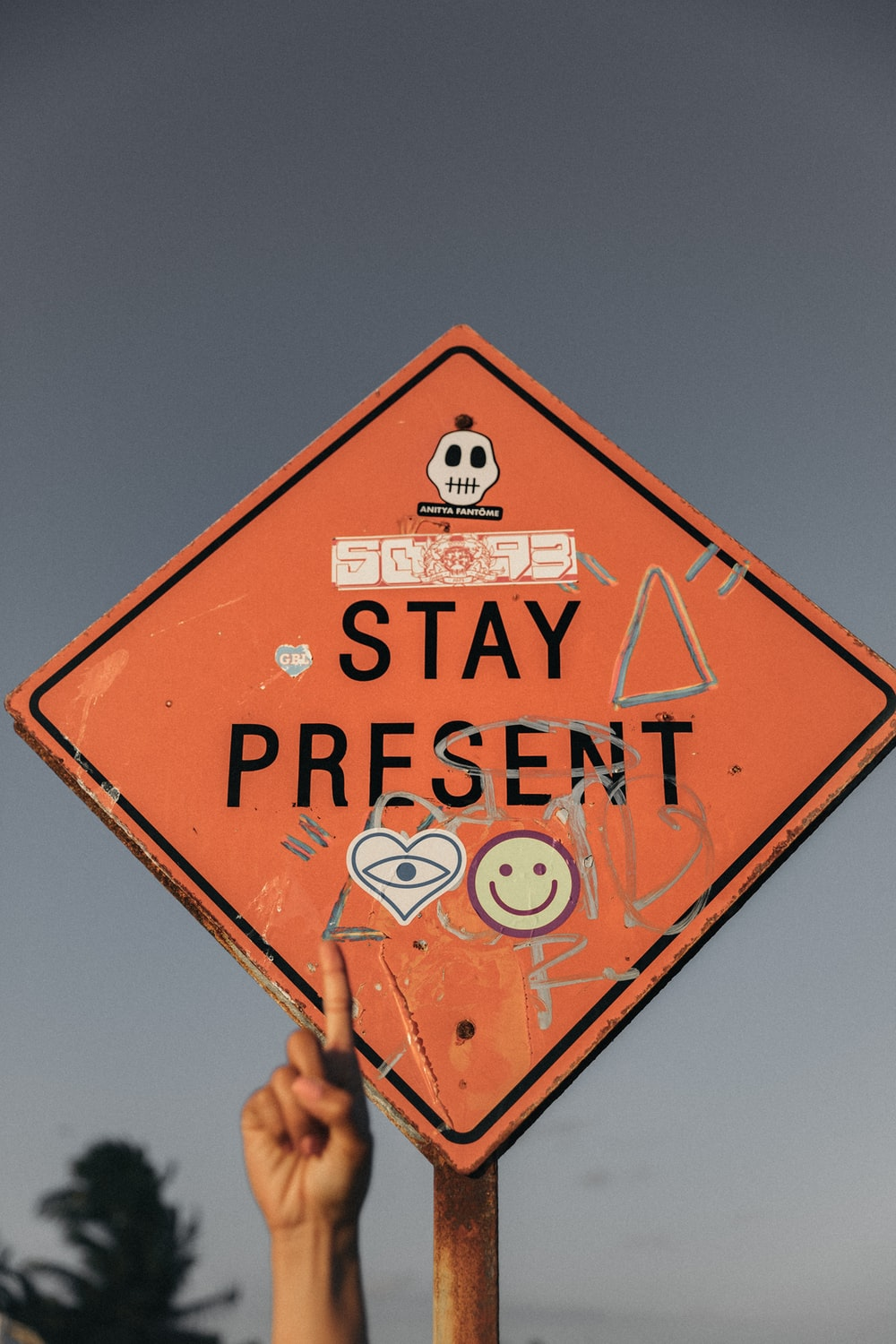 person pointing Stay Present road sign during daytime