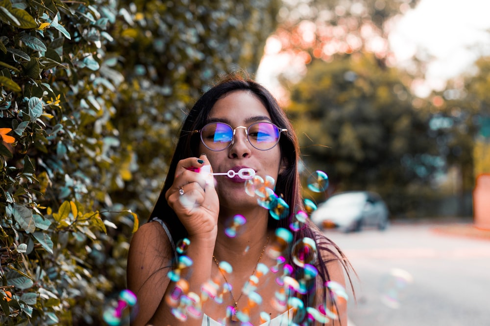 woman blowing bubble outdoor during daytime