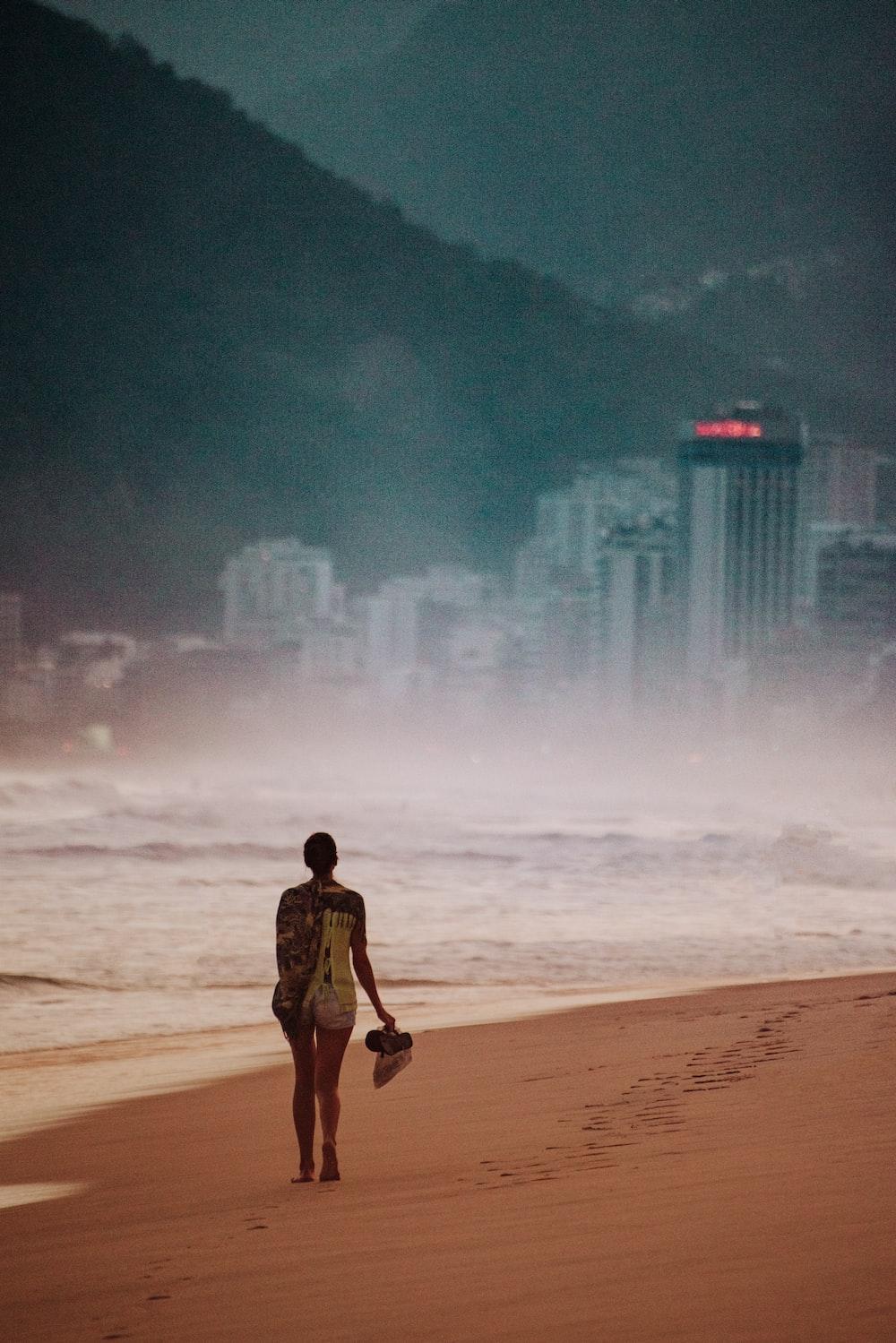 girl walking on seashore across city building