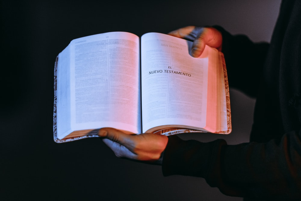 person holding book showing Nuevo Testamento