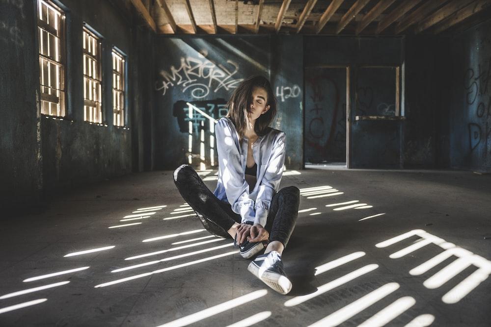 woman wearing blue jacket sitting on floor