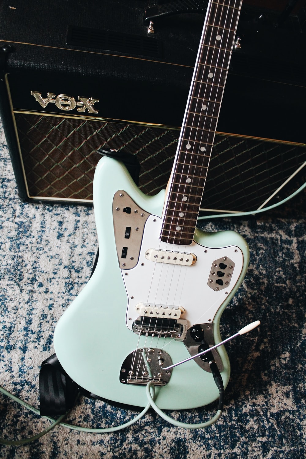 teal and white electric guitar near amplifier