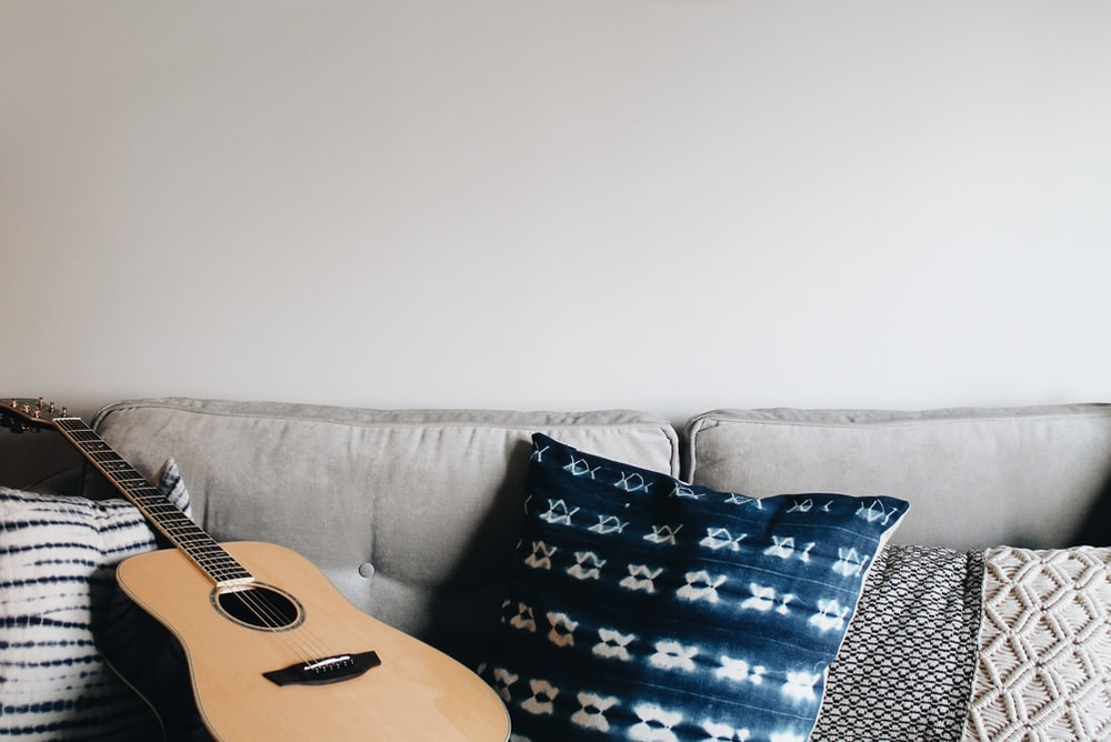 brown acoustic guitar near throw pillow on sofa