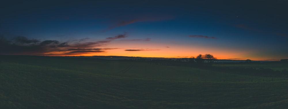 orange setting sun across ffiels