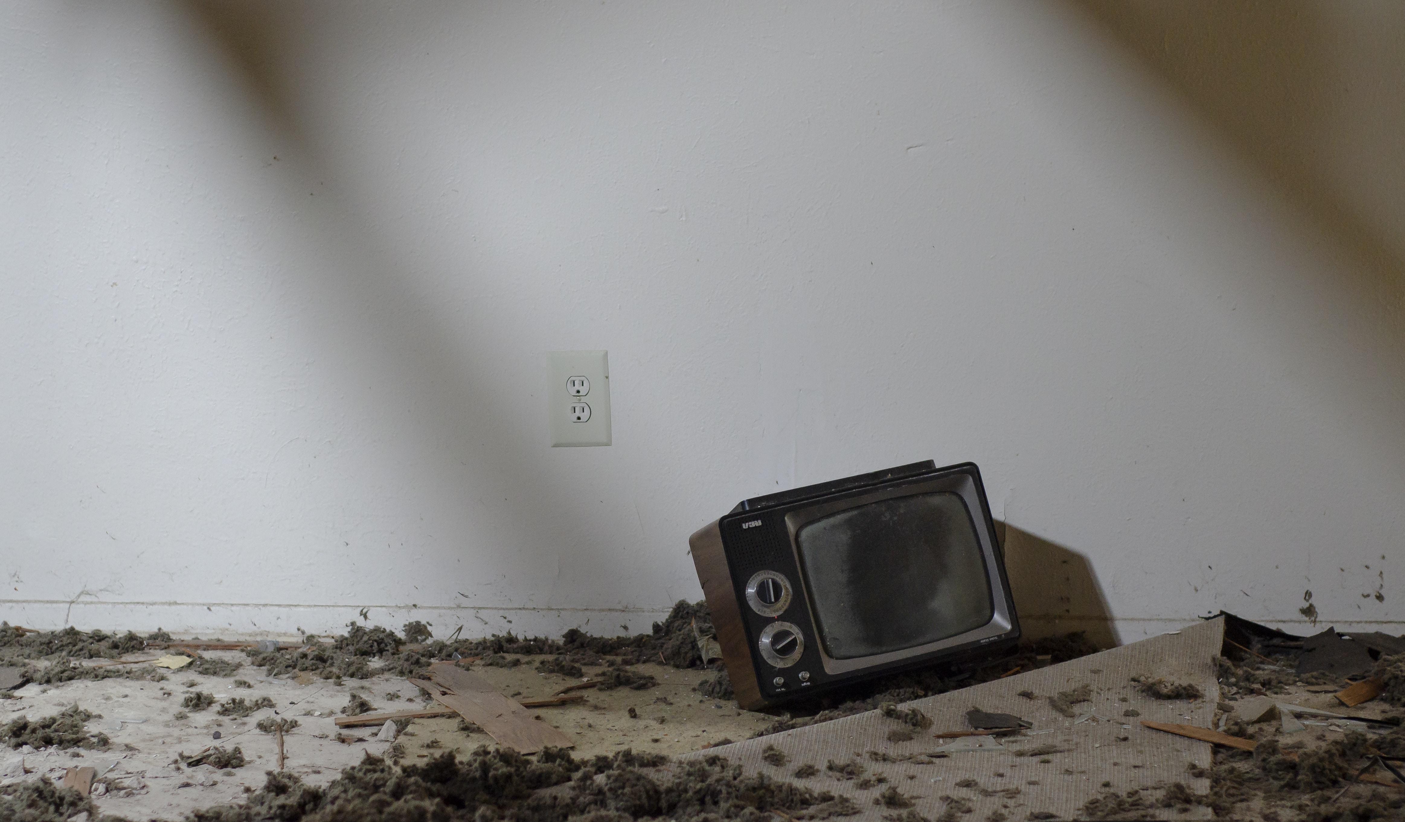 vintage black television on floor with debris