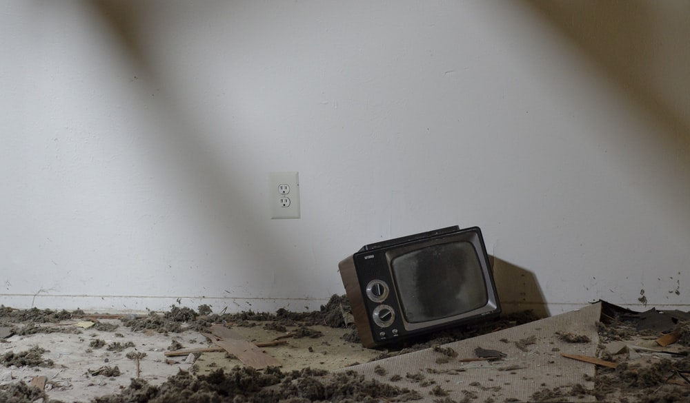 vintage black television on floor with debris