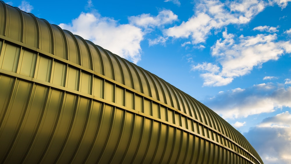 white clouds in blue sky over gold-colored metal structure