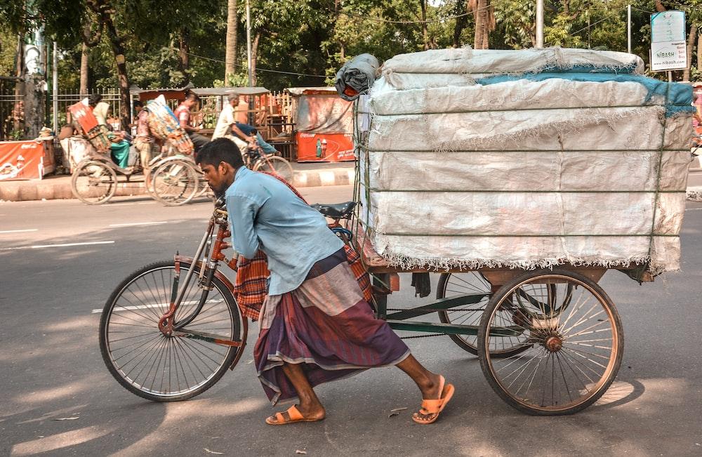 man pushing trike loaded with saks