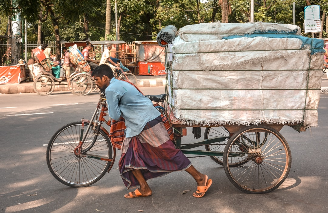 A man pushing a trishaw with a heavy load in the street of Dhaka, Bangladesh.