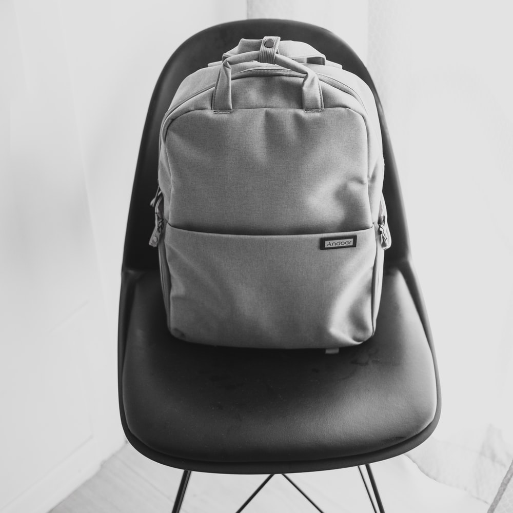 grayscale photography of backpack on chair