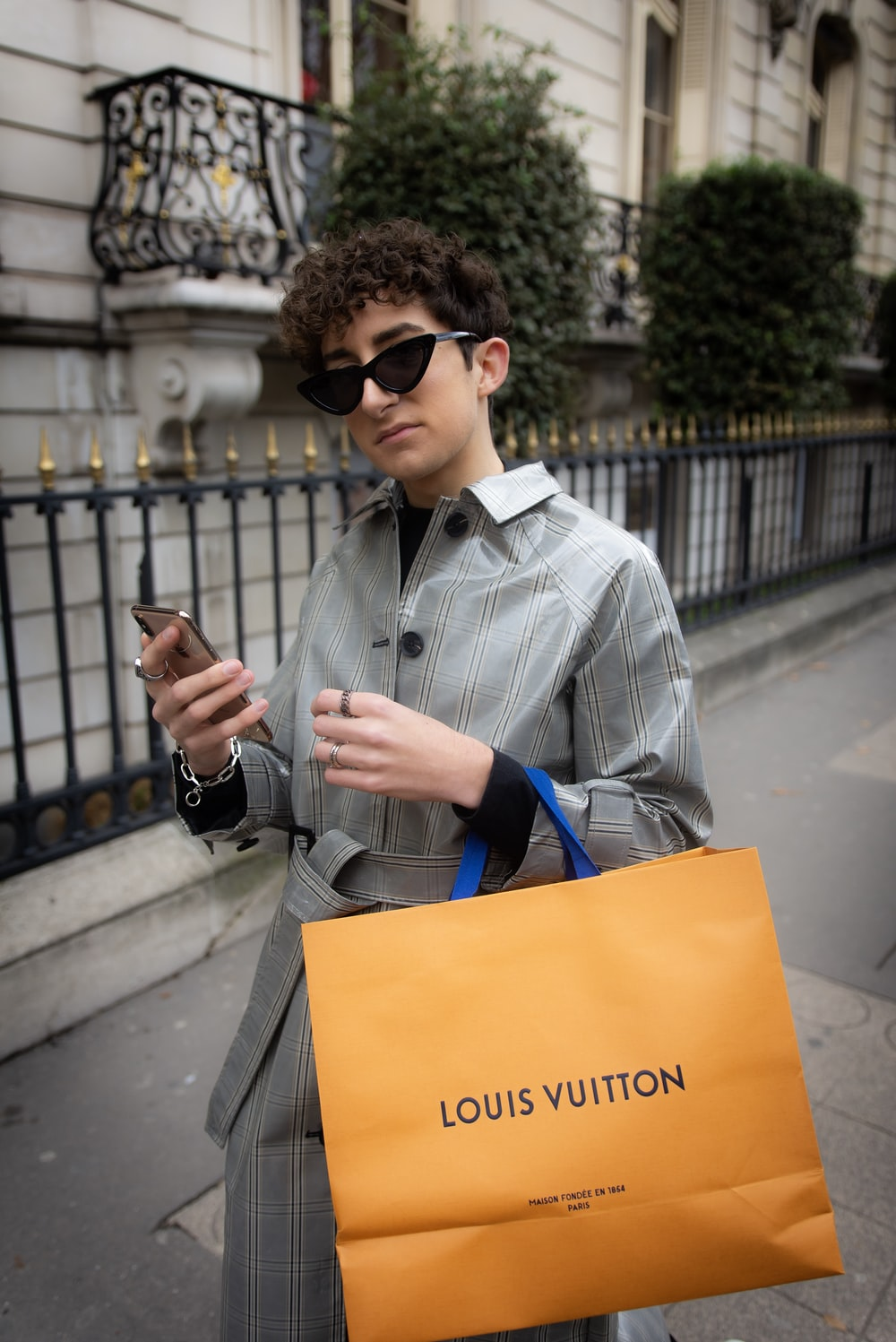 standing person carrying Louis Vuitton shopping bag