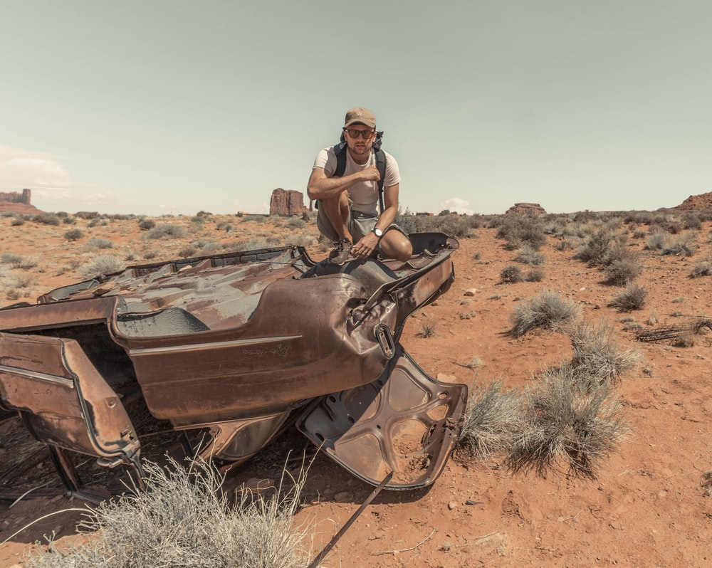 man sitting on brown wrecked vehicle