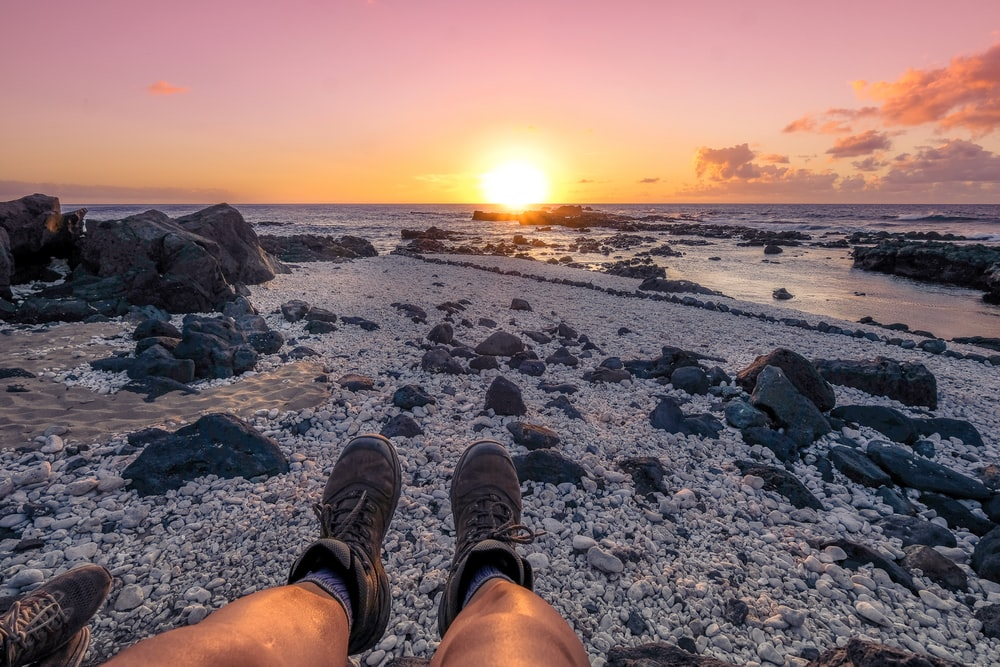 sitting person wearing brown pants overlooking sea during golden hour