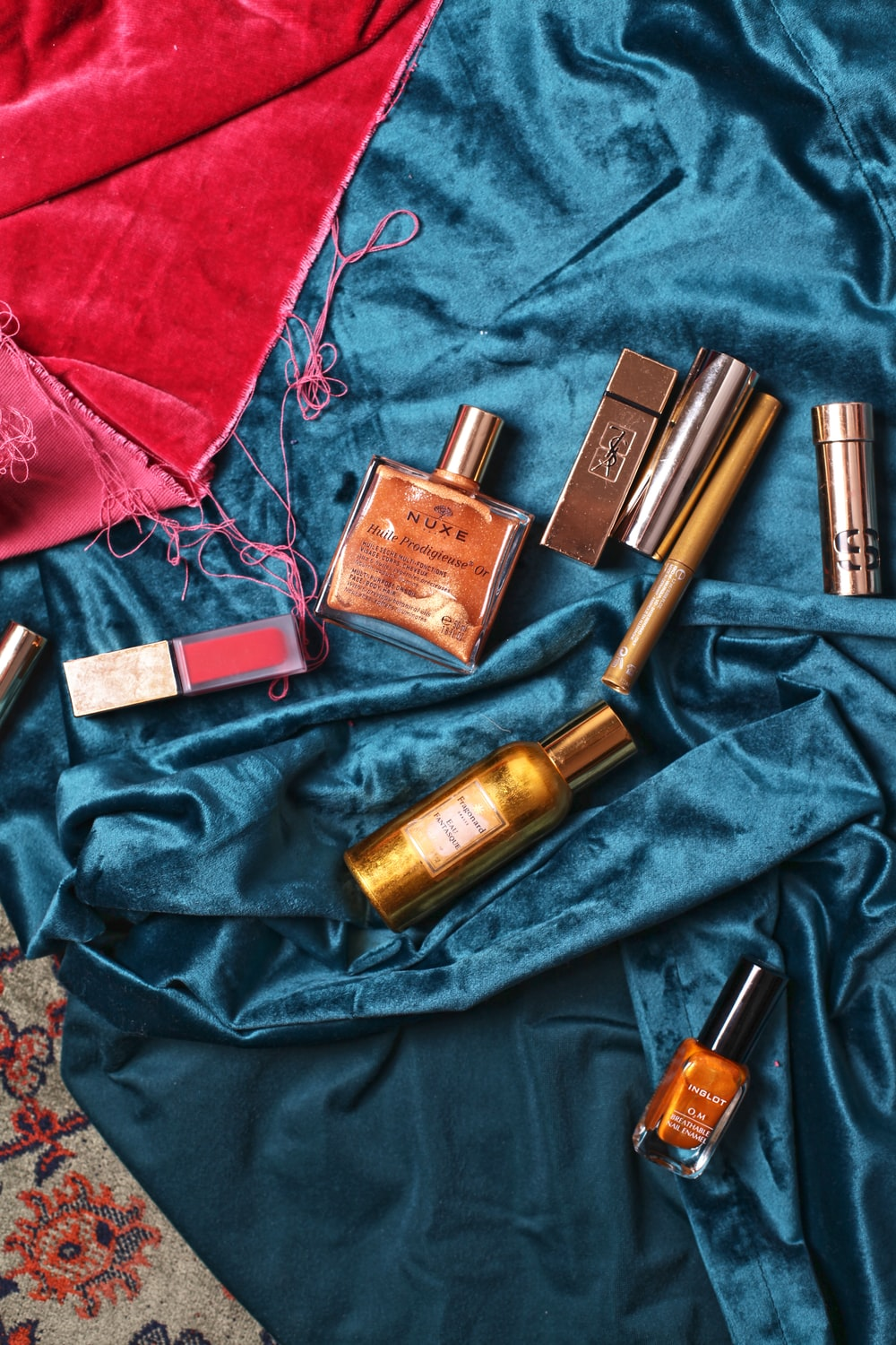 assorted cosmetics on teal textile