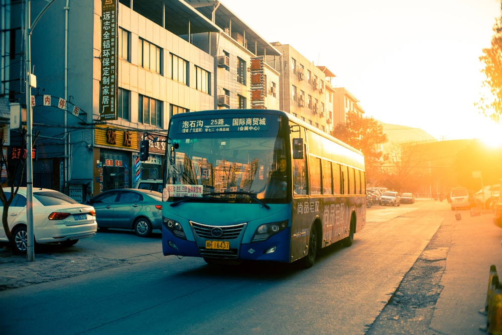 ゴールデンアワー中にアスファルト道路の青いバス
