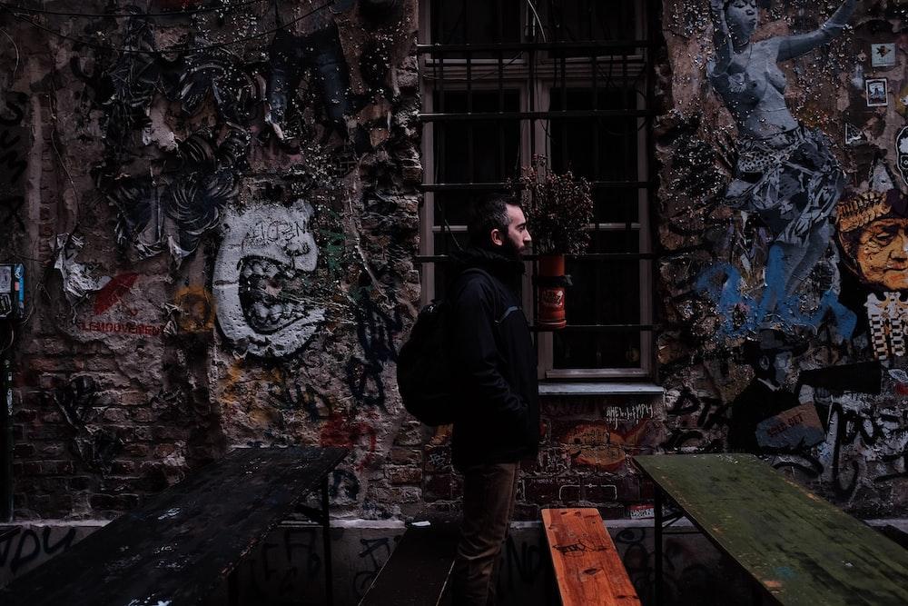 man standing beside concrete building