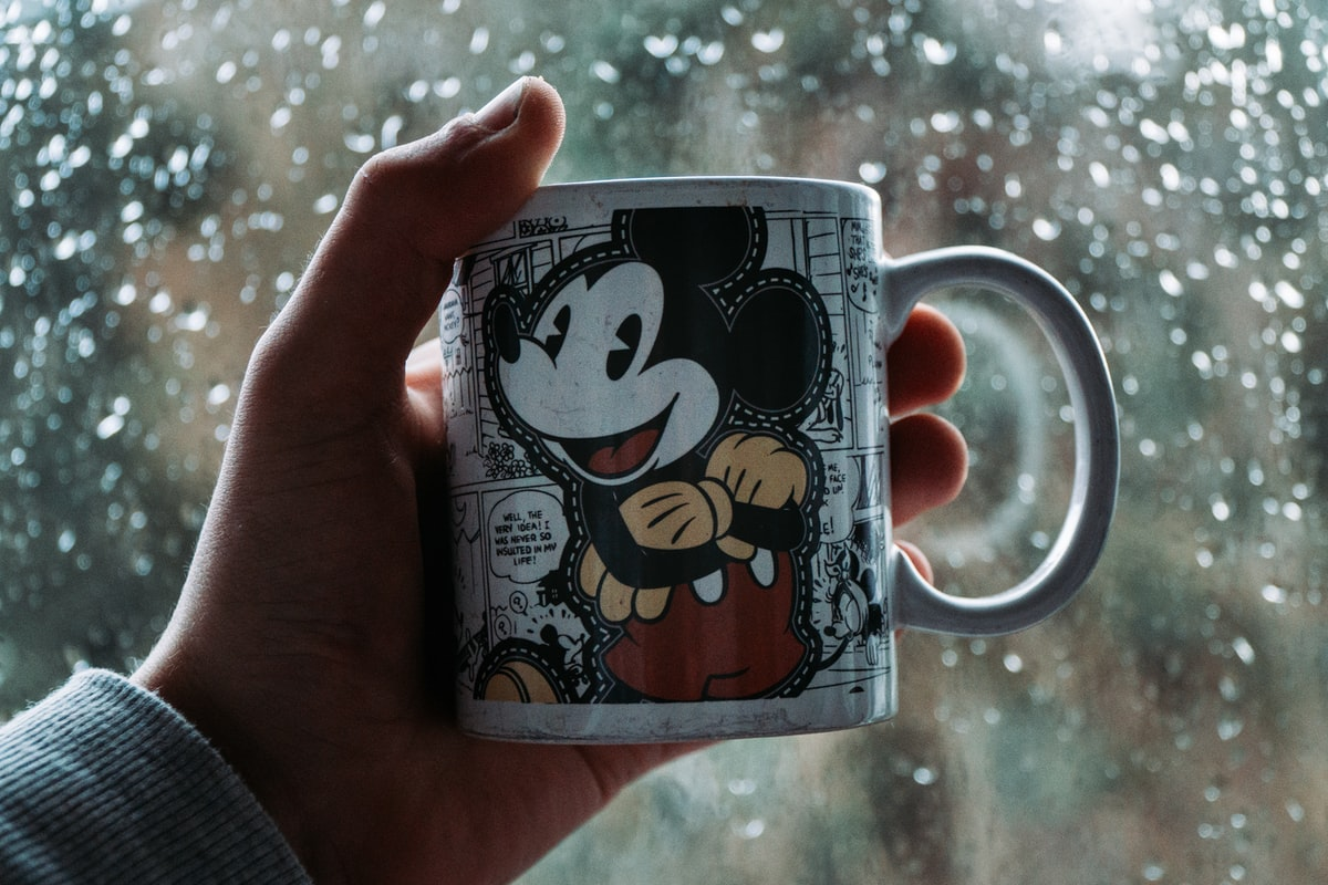 person holding a mickey mouse coffee mug