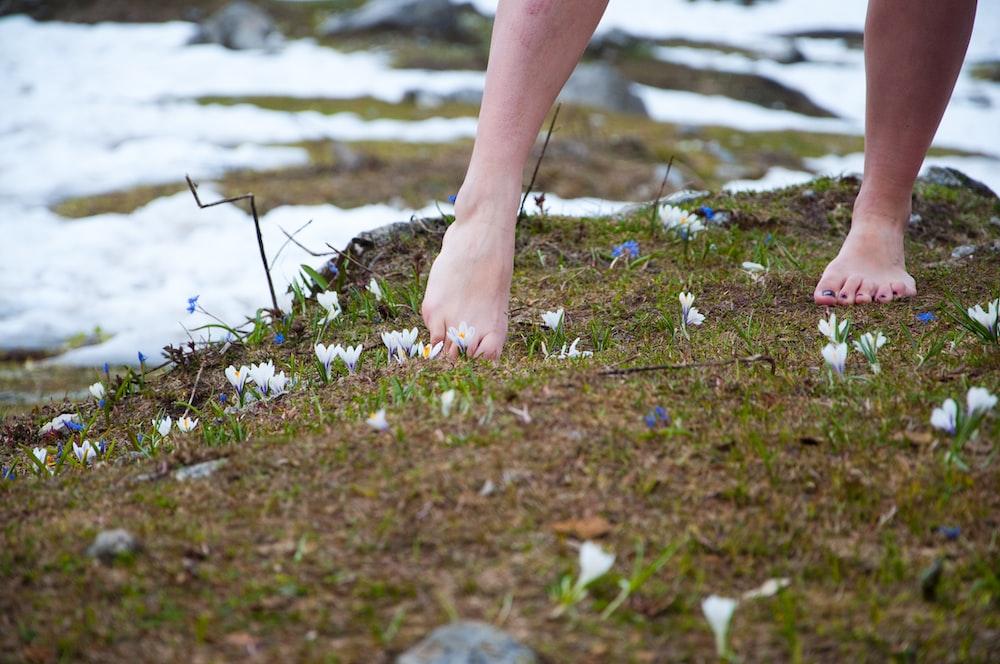 barefoot woman on green grass field