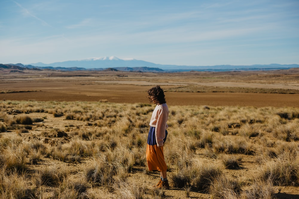 woman standing on brown grasses