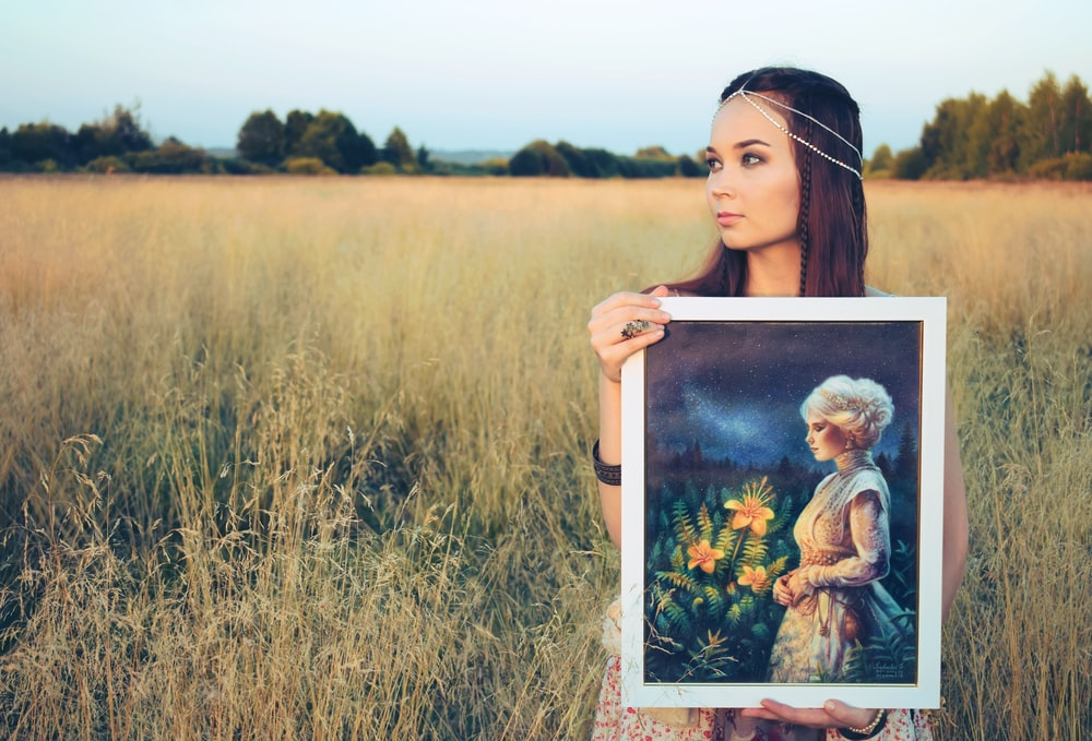 woman holding painting of woman
