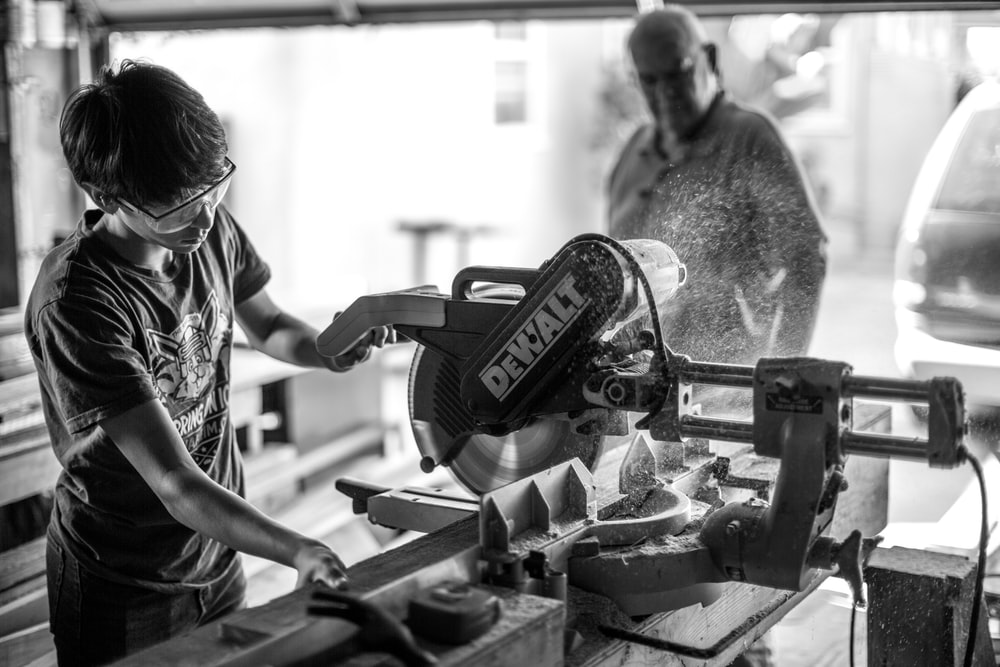 grayscale photography of boy using miter saw