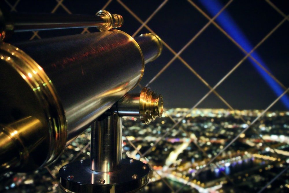 brass-colored telescope overlooking city at night
