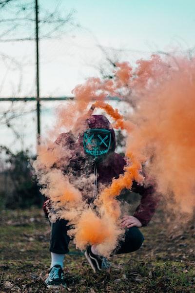 person in purple hoodie releasing orange smoke
