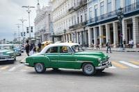 green sedan on road during daytime