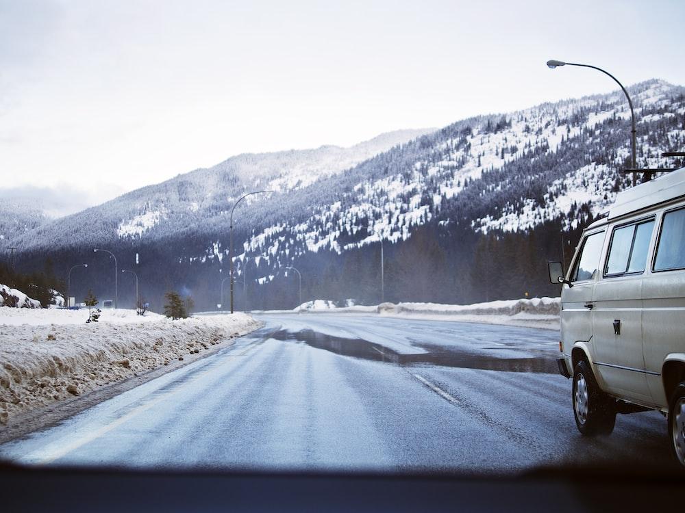 white van crossing road during daytime
