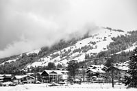 grayscale photography of village with mountain background