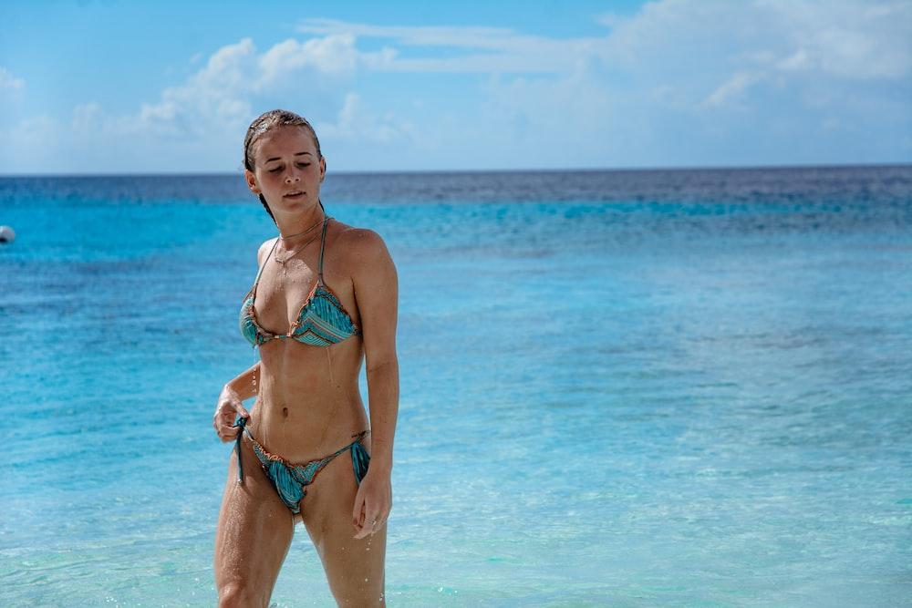 woman on seashore wearing blue bikini