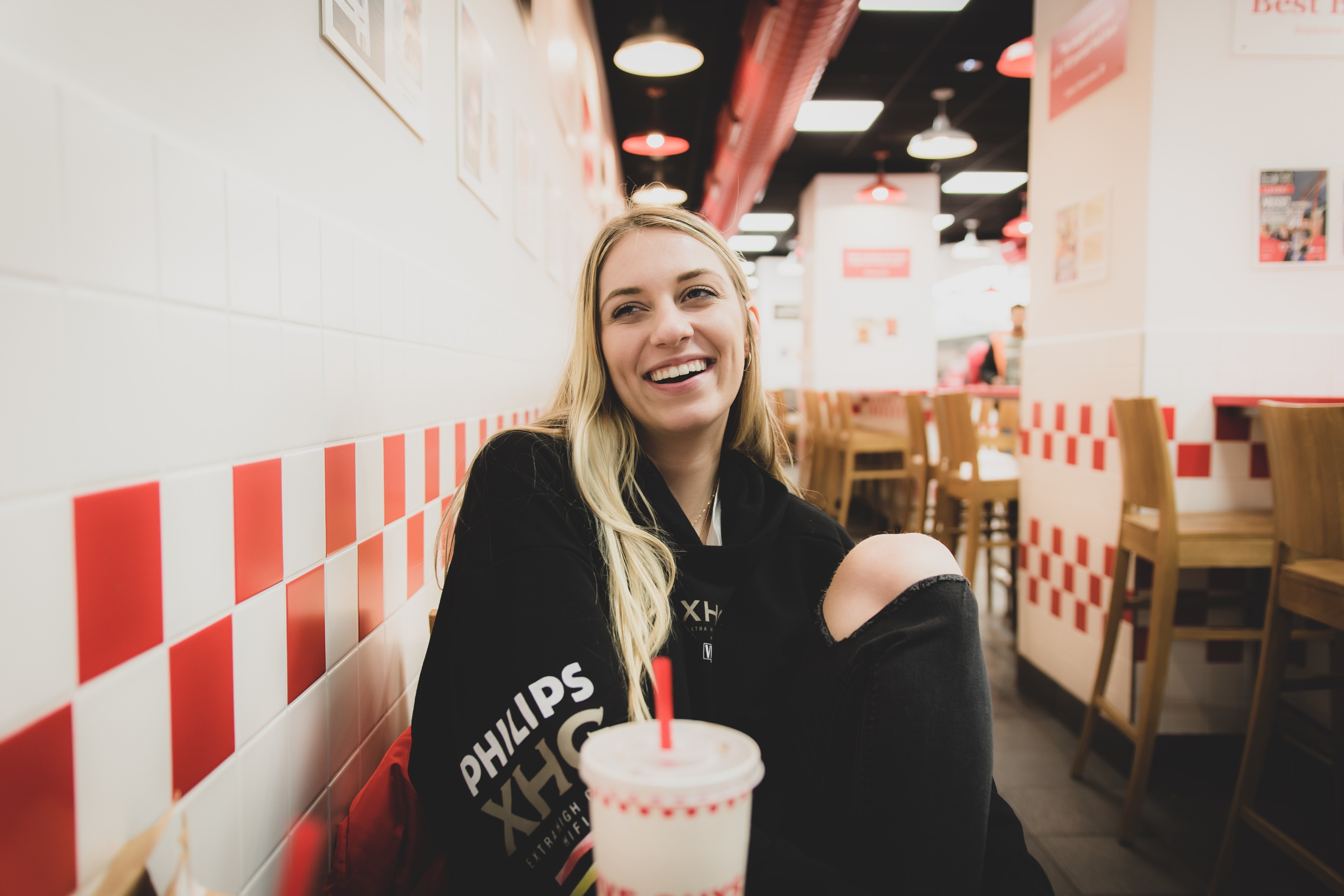 laughing woman sitting against the wall in food court