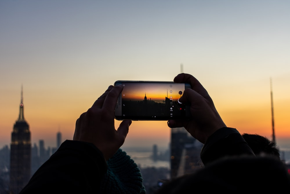 person holding smartphone while taking picture of tower