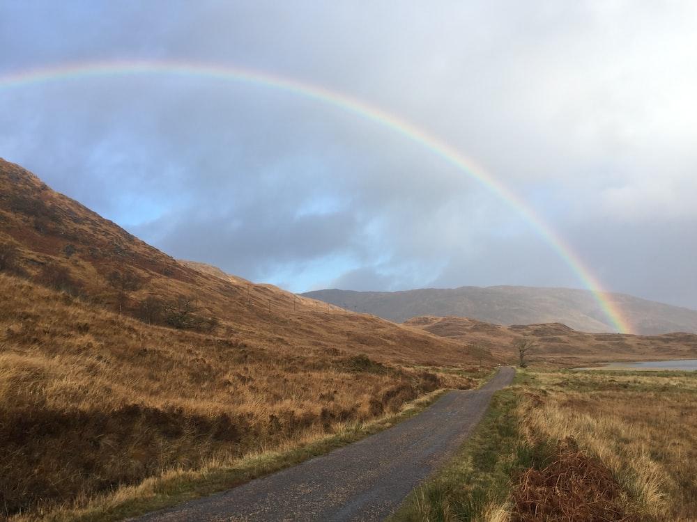 landscape photo of mountains under rainbow