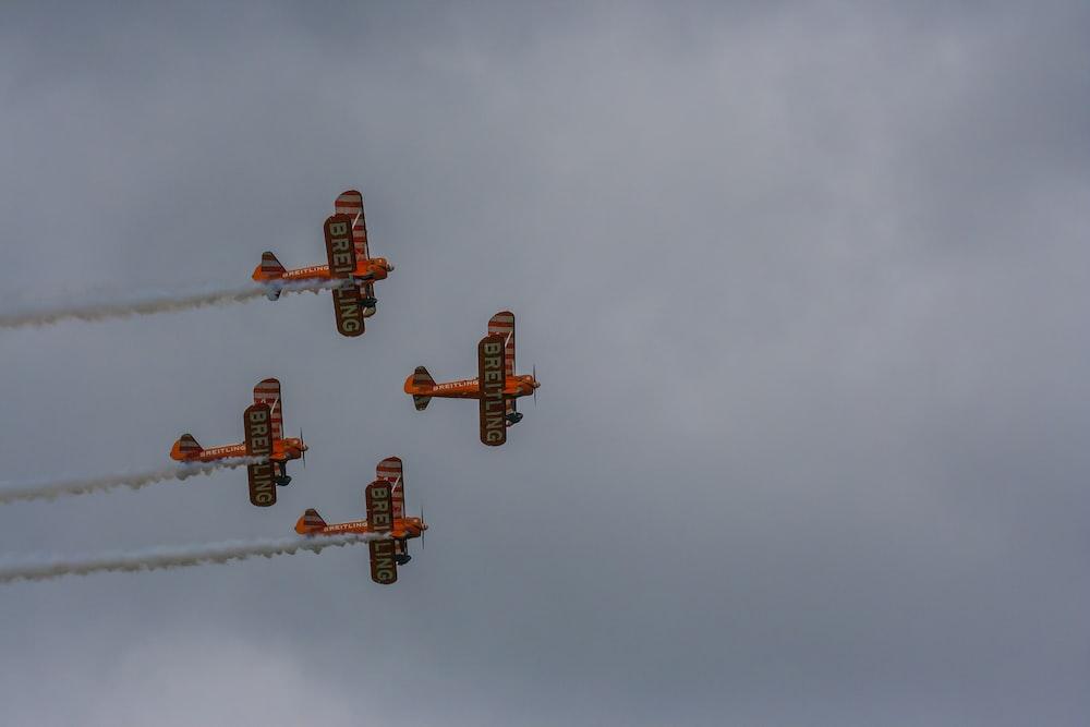 four orange biplanes flying in sky