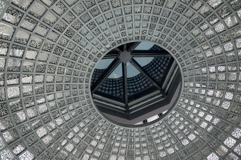 low-angle photo of grey and white concrete dome ceiling