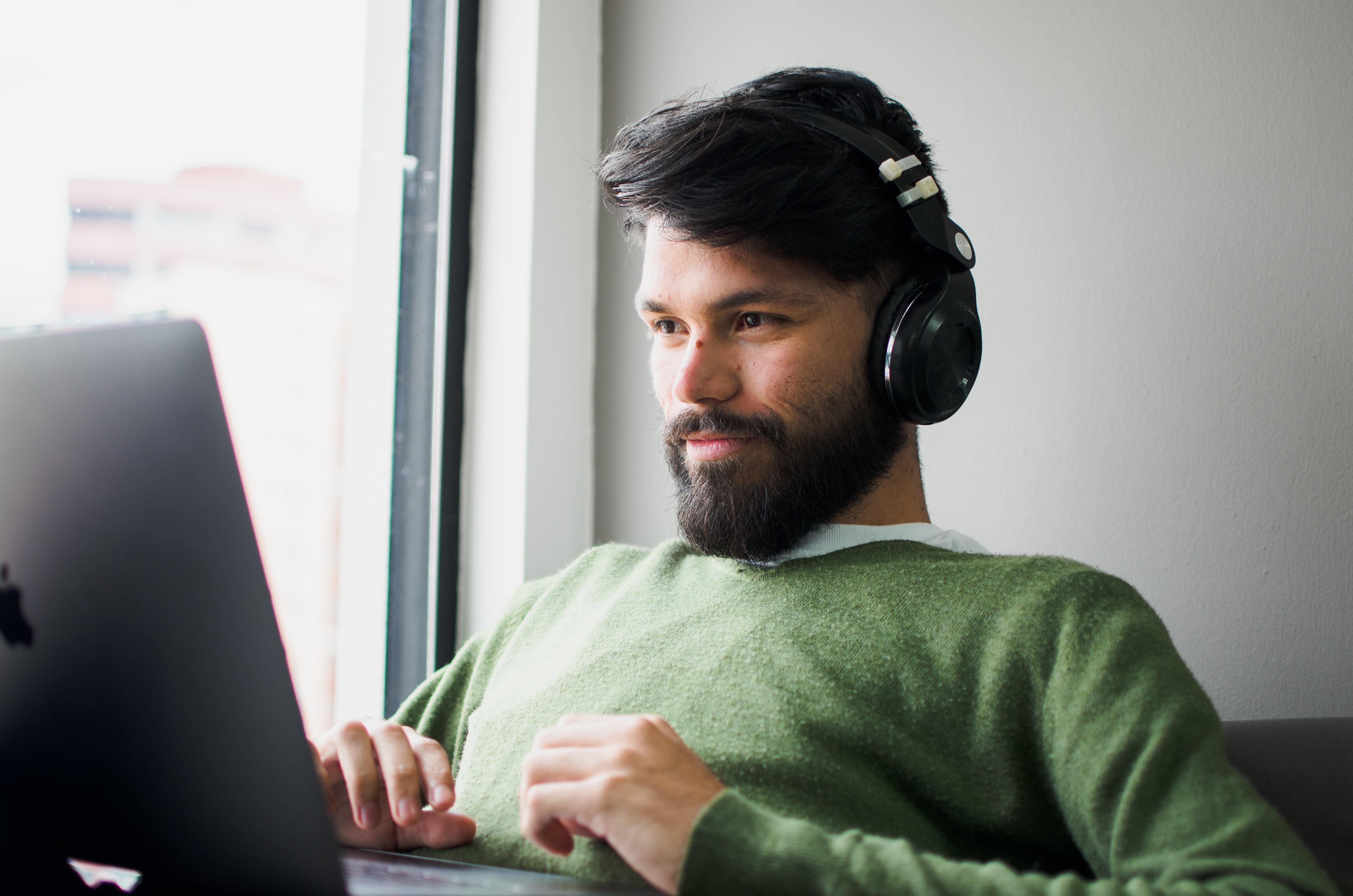 man wearing headphones while looking at MacBook