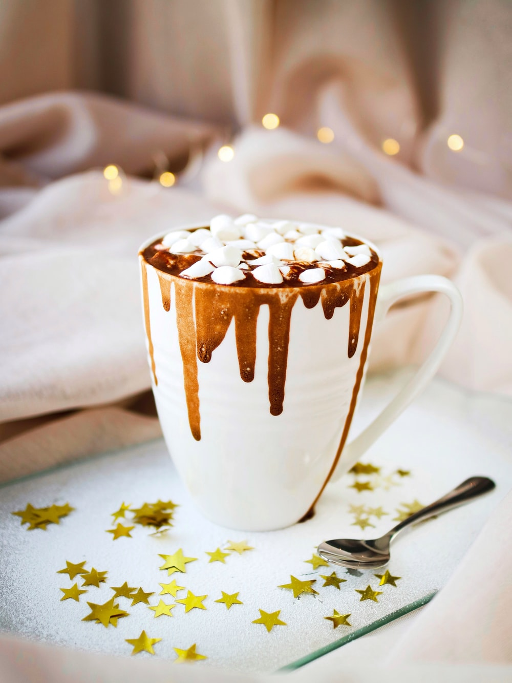 white mug with brown liquid topped with marshmallows