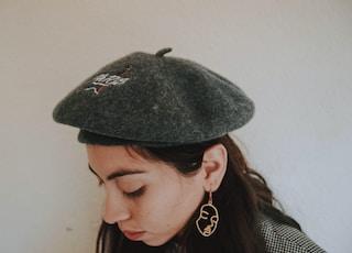 woman wearing gray hat standing beside wall