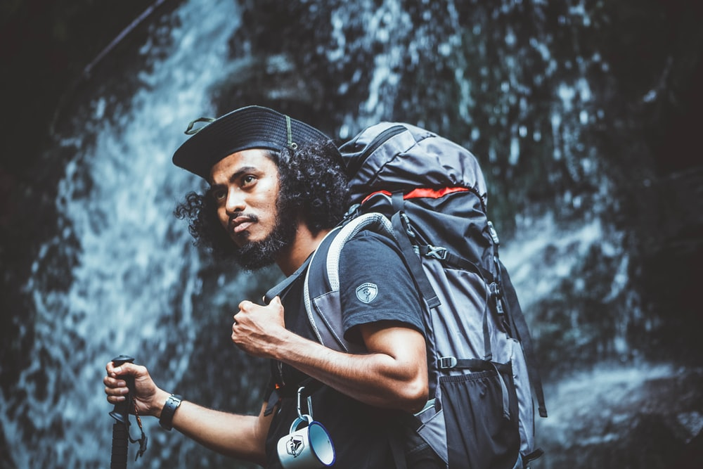 selective focus photography of man near waterfalls during daytime