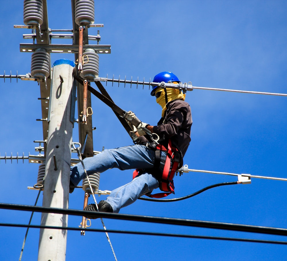 selective photography of electrician on electric pole during daytime