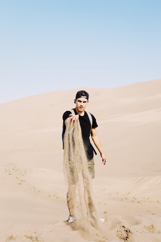 man in black shirt standing on desert lang