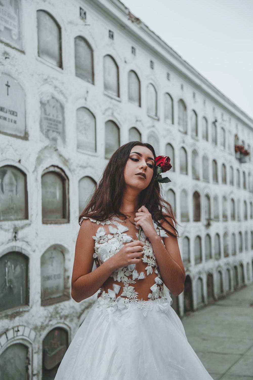 woman wearing wedding dress standing beside tombstone