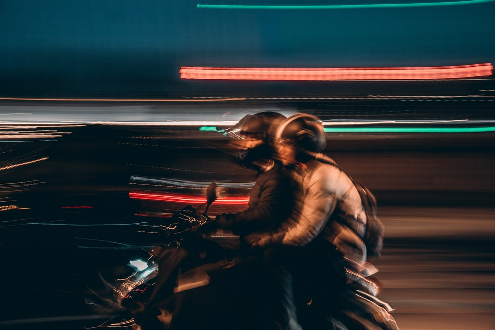 time lapse photography of two people riding motorcycle