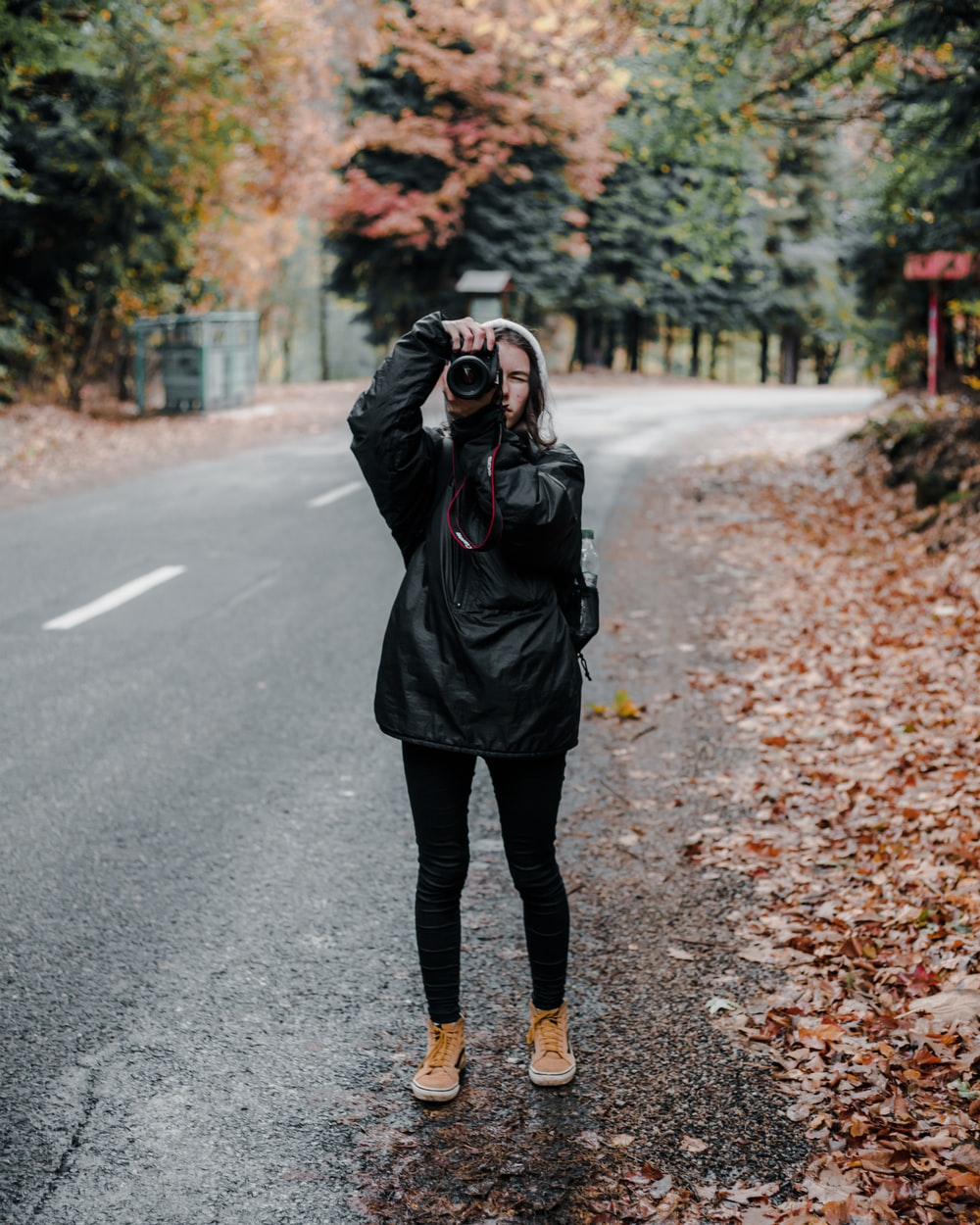 man holding camera standing on road