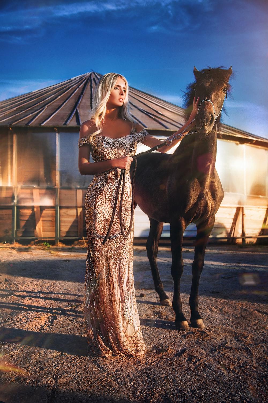 woman wearing brown dress standing beside horse