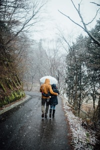 man and woman walking in the rain while holding umbrella