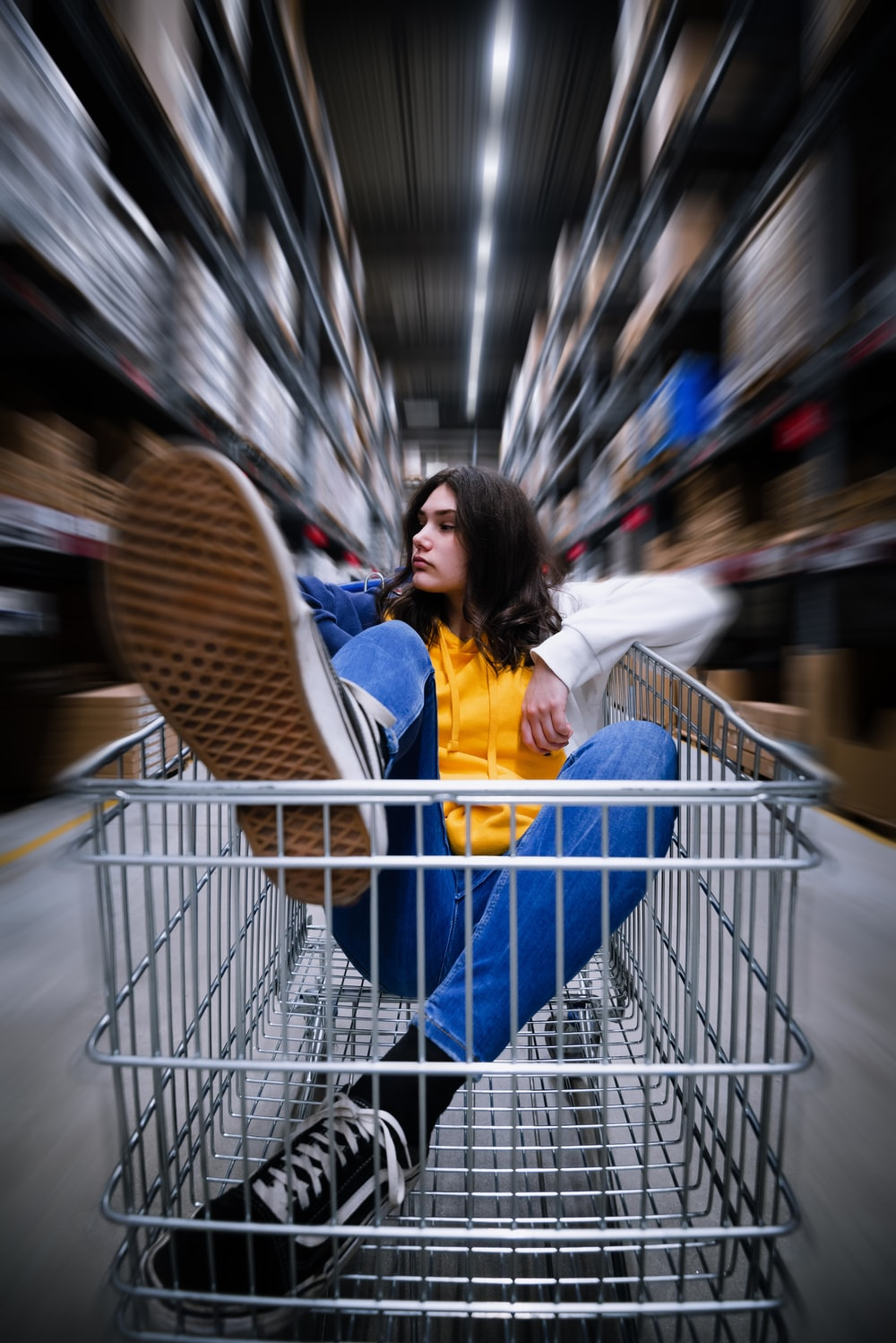 selective photography of woman riding shopping cart in warehouse