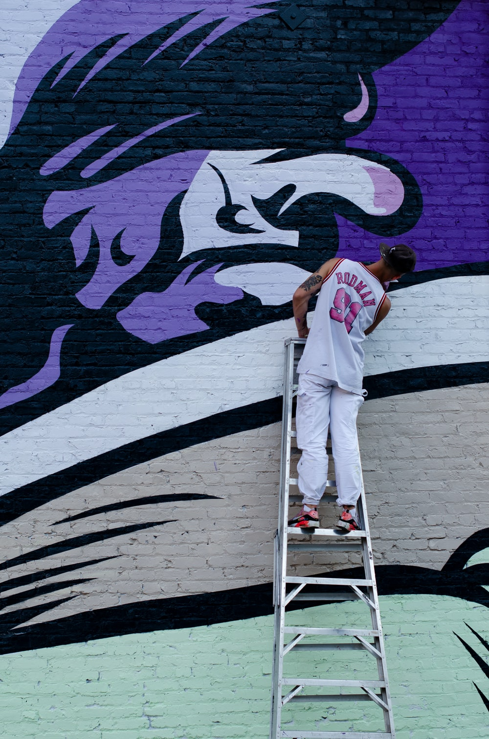 man standing on ladder and painting the wall